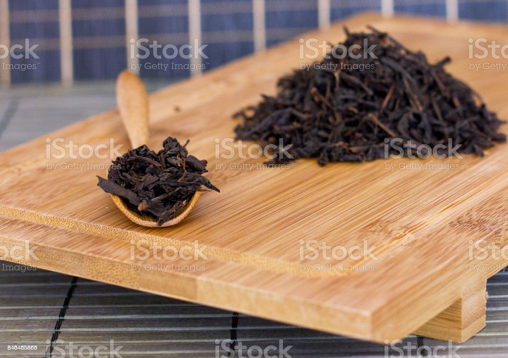 Black friable tea in a wooden spoon on the wooden tray stock photo