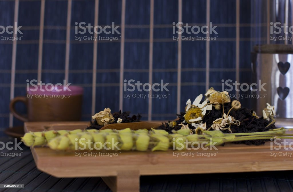 Black friable tea with the sage salvia and chamomile. On the wooden spoon on tray stock photo
