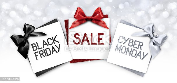 670414478 istock photo black friday and cyberg monday sale text write on gift card label with black, red and silver ribbon bow on blurred bright lights background 877030224