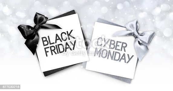 670414478 istock photo black friday and cyberg monday text write on gift card label with black and silver ribbon bow on blurred bright lights background 877030218