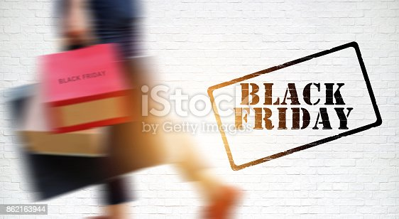 istock Black Friday, Blurred woman shopper with shopping bag walking on the white brick wall background 862163944