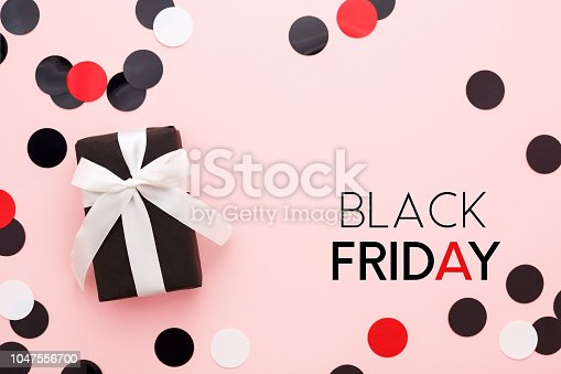 istock Black friday card with gift box and confetti on pink background. 1047556700