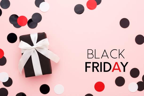 carton de vendredi noir avec boîte-cadeau et de confettis sur fond rose. - black friday photos et images de collection