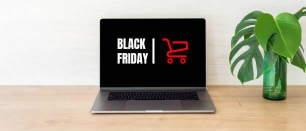 """concepto del viernes negro. pantalla de ordenador portátil con tarjeta de compra y signo """"viernes negro"""" en el escritorio de madera - black friday sale fotografías e imágenes de stock"""