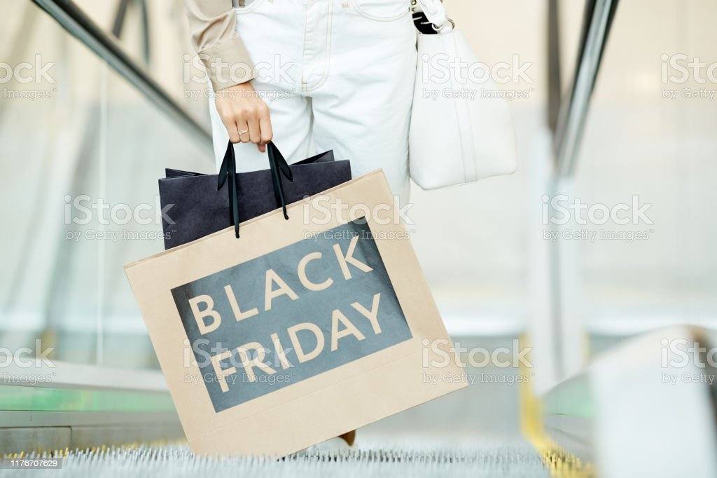 Black friday in shopping mall Close-up of young woman holding shopping bags while standing on escalator during black friday in the shop Adult Stock Photo