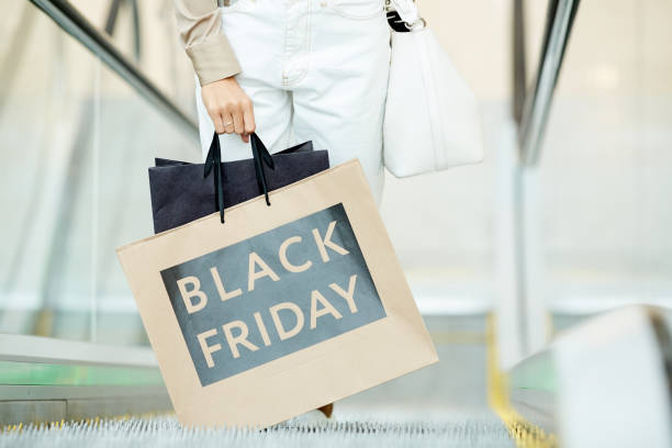 Black friday in shopping mall Close-up of young woman holding shopping bags while standing on escalator during black friday in the shop black friday stock pictures, royalty-free photos & images