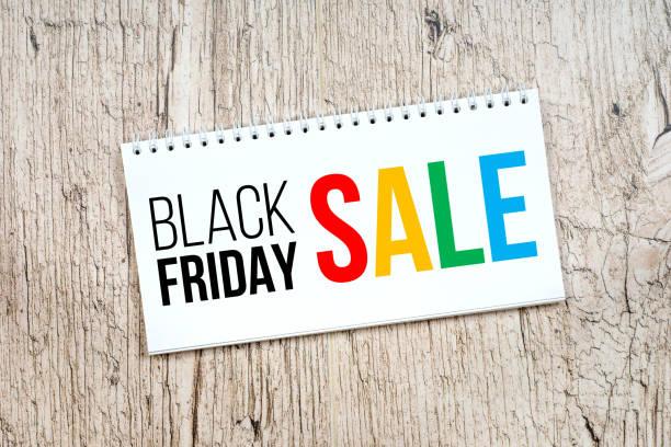 schwarzer freitag-verkauf, schwarzen und farbigen text im editor auf weißem rustikalen tisch - laminat günstig stock-fotos und bilder