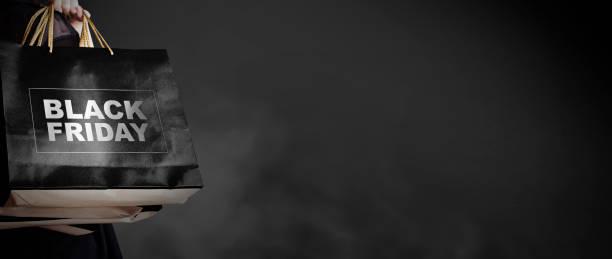 concept de vente vendredi de jeune femme tenant le sac à provisions sur fond sombre avec style de mode copie espace de noir - black friday photos et images de collection