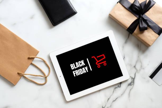 """concept de vente de vendredi noir. tablette avec signe """"vendredi noir"""", boîte cadeau, sac à provisions sur table en marbre. laïc plat, vue du haut, frais généraux - black friday photos et images de collection"""
