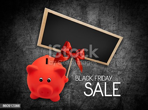 670414478 istock photo Black Friday sale text blackboard and piggy bank with red ribbon bow on black background 860912066