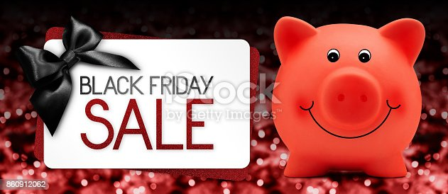 670414478 istock photo Black Friday sale text write on gift card label with red piggy bank and black ribbon bow on blurred bright lights background 860912062