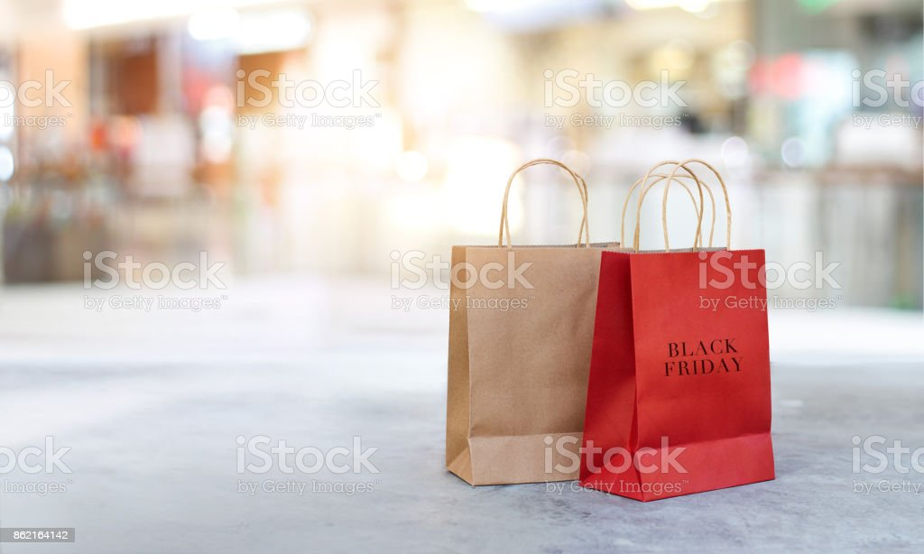 Black Friday shopping bags on the floor outdoors of shopping mall background stock photo