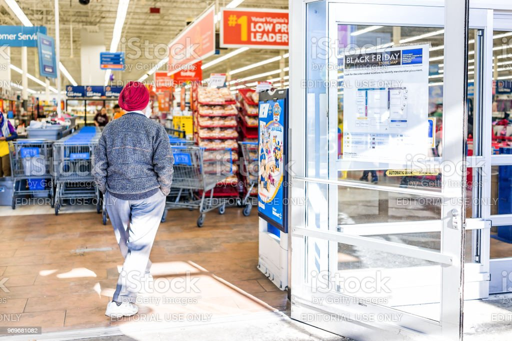 Black Friday sign in Walmart store entrance with map after Thanksgiving shopping consumerism in Virginia with sikh man walking inside stock photo