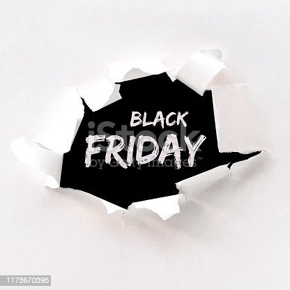 Black friday text in paper hole teared in white paper over black background. Flat lay, overhead angle, square composition