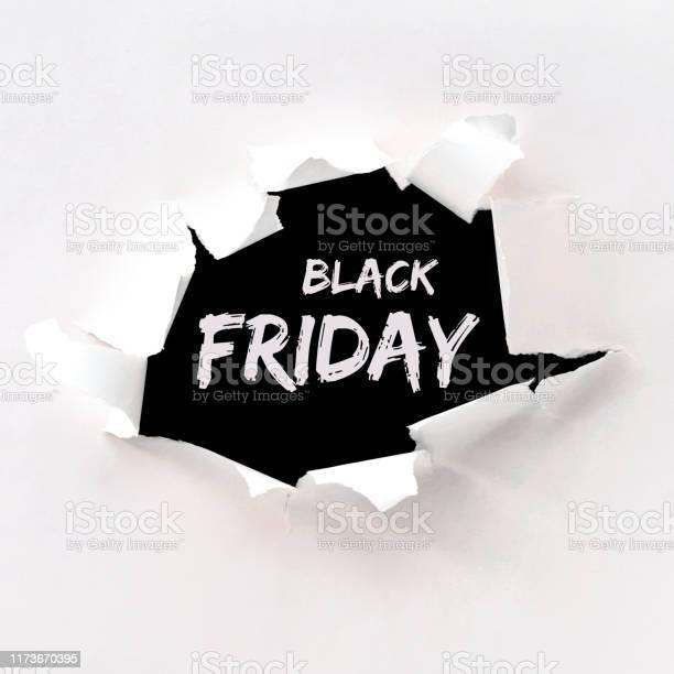 Black Friday Text In Paper Hole Teared In White Paper Over Black Background - Fotografias de stock e mais imagens de Abstrato