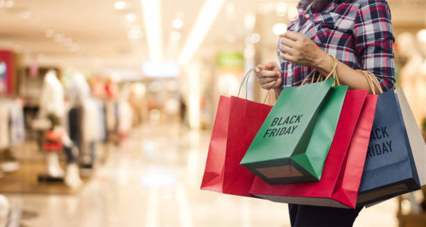 black friday, woman holding many shopping bags while walking in the shopping mall background. - black friday imagens e fotografias de stock