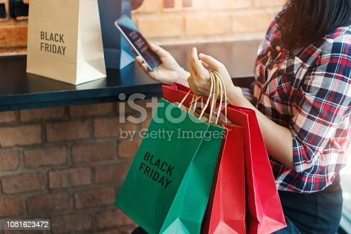 istock Black Friday, Woman using smartphone and holding shopping bag while sitting in the mall background 1051623472