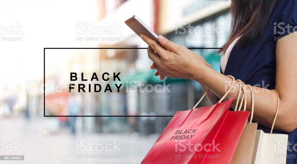 Black Friday, donna che usa lo smartphone e tiene la borsa della spesa mentre si trova sullo sfondo del centro commerciale - Foto stock royalty-free di Adulto