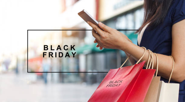 Black Friday, Woman using smartphone and holding shopping bag while standing on shopping  mall background stock photo
