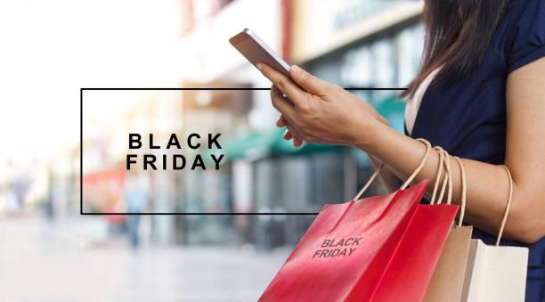 black friday, frau mit smartphone und einkaufszentrum hintergrund einkaufstasche beim stehen festhalten - heute ist freitag stock-fotos und bilder