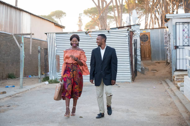 Black friends walking together through the township stock photo