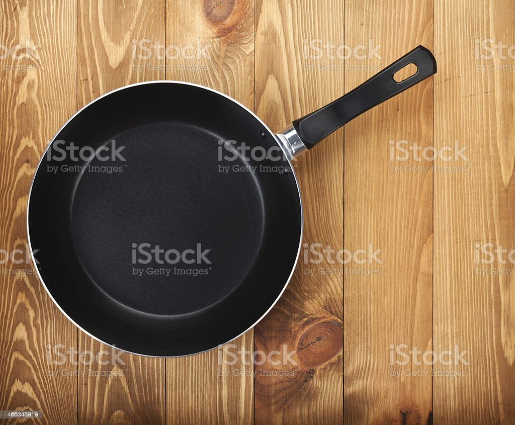 A black frying pan on a wooden table stock photo