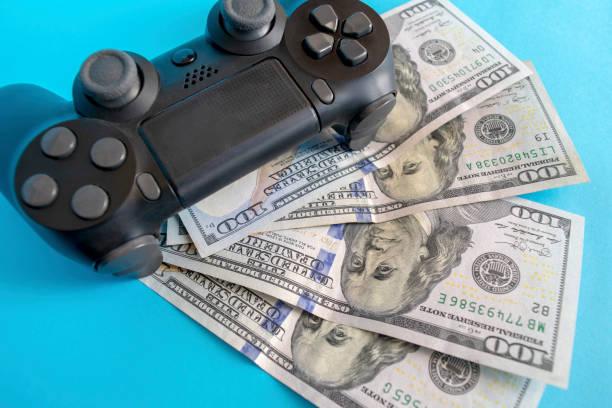 Black game joystick with us dollars on blue background stock photo