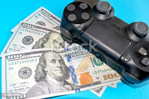 Black game joystick with US dollars on blue background. Playing for money concept. Game pad with money. People earn money by playing computer games.
