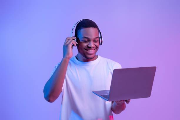 Black Gamer Man In Headset Playing Video Games On Laptop, Neon Lighting stock photo