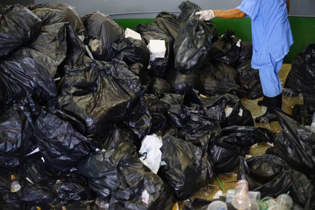 Sacos de lixo pretos no hospital, pilha de resíduos plásticos. - foto de acervo
