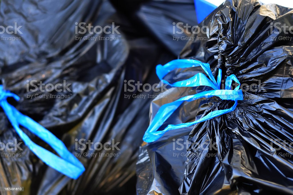 Black garbage bags tied with blue strings stock photo