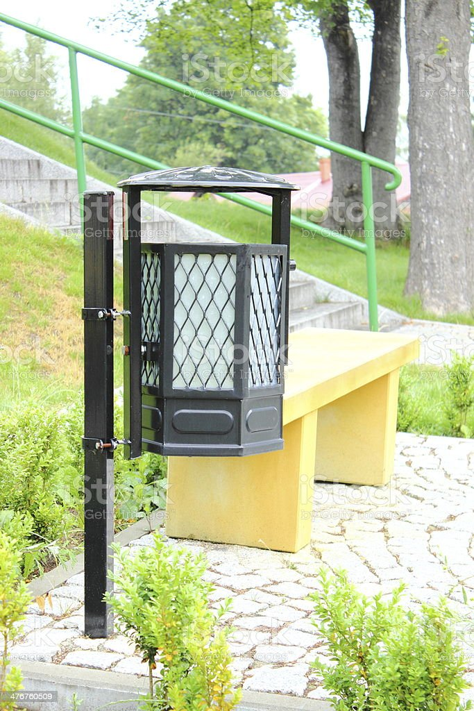 Black garbage basket and yellow bench in a park royalty-free stock photo