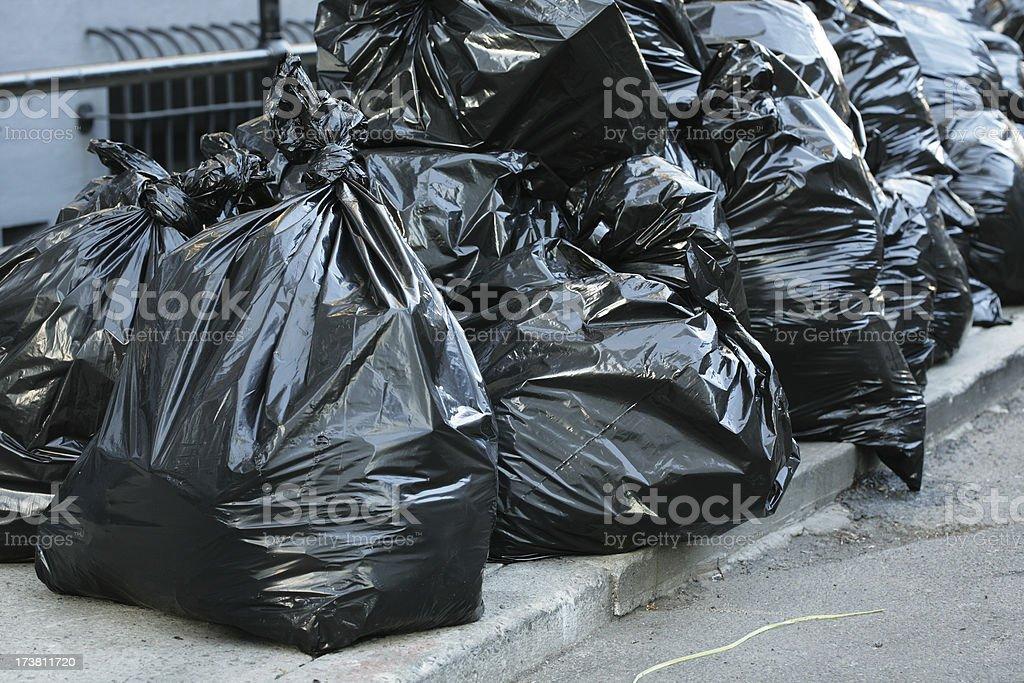 Black Garbage Trash Bags by Street Curb royalty-free stock photo