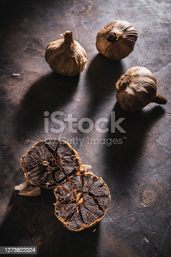 Black garlic aged bulbs and cloves on a dark moody vintage background