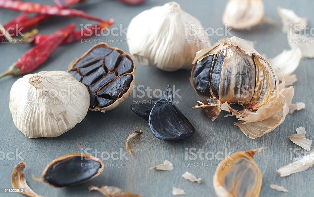 Black garlic artistically scattered on grey background stock photo