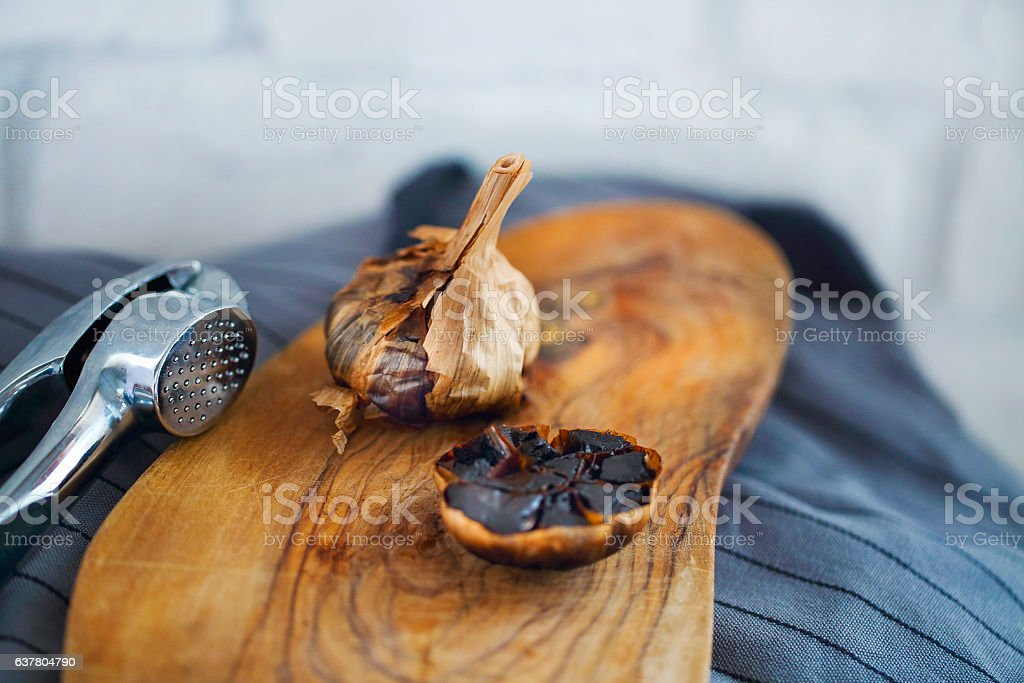 Black garlic bulbs and cloves on wooden background stock photo