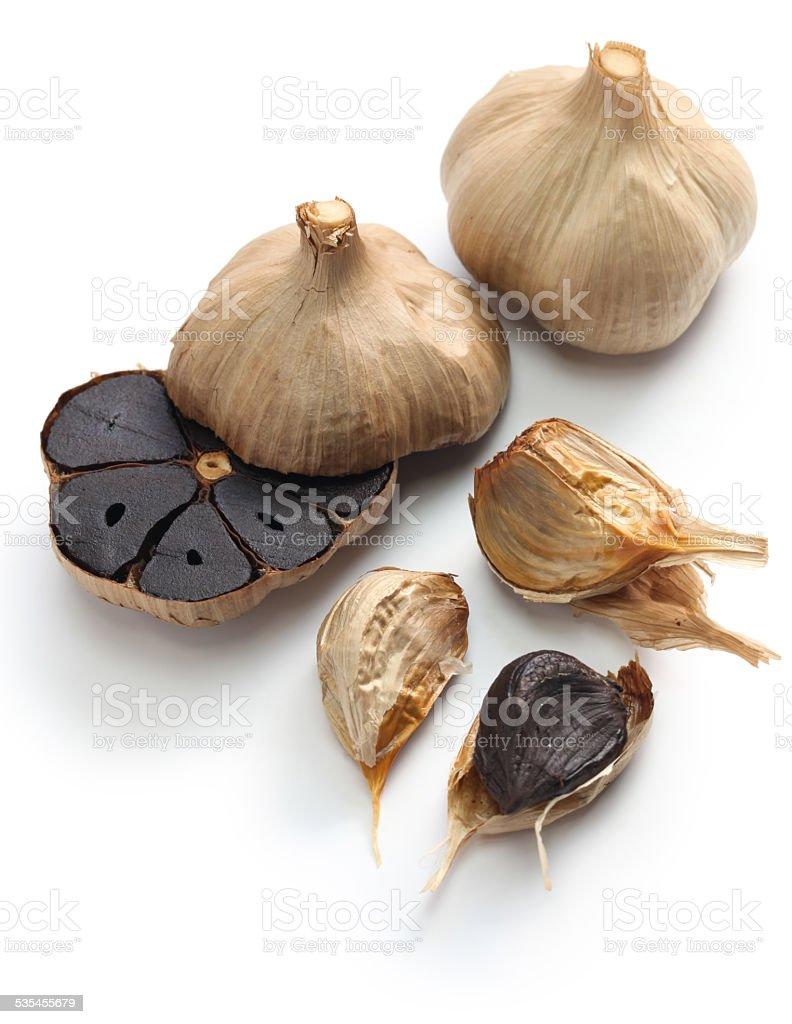 black garlic bulbs and cloves stock photo