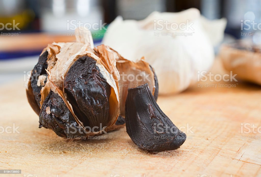Black garlic opened in kitchen table stock photo