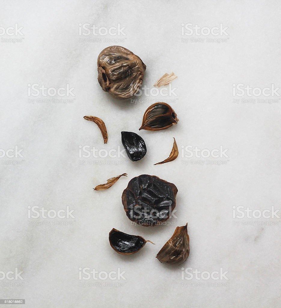 Black garlic overhead on marble stock photo