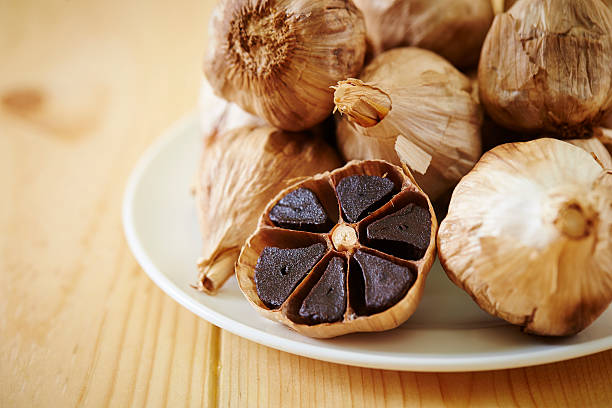 black garlic - garlic stock photos and pictures