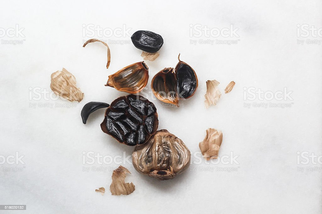 Black garlic scattered on marble stock photo