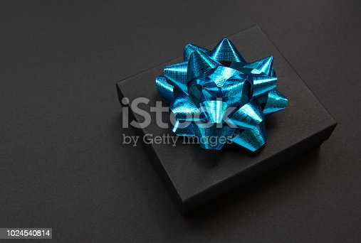 istock Black gift box on a dark contrasted background, decorated with a blue color bow, creating a romantic atmosphere. Typically used for birthday, anniversary presents, gift cards, post cards. 1024540814