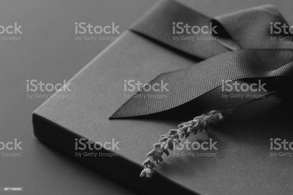 Caixa de presente preta sobre um fundo escuro e contrastada, decorado com um laço texturizado e penas, criando uma atmosfera romântica. Normalmente usado para aniversário, presentes de aniversário, cartões de presente, cartões postais, cartas. - foto de acervo