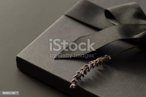 istock Black gift box on a dark contrasted background, decorated with a textured bow and feathers, creating a romantic atmosphere. Typically used for birthday, anniversary presents, gift cards, post cards. 959323672