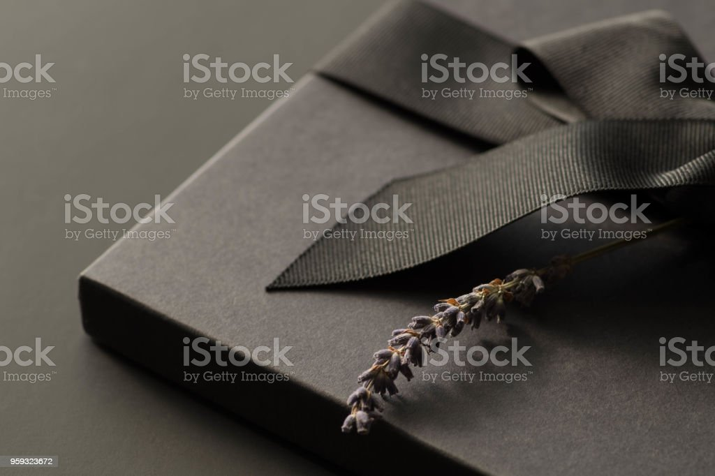 Caixa de presente preta sobre um fundo escuro e contrastada, decorado com um laço texturizado e penas, criando uma atmosfera romântica. Normalmente usado para aniversário, aniversário presentes, cartões de presente, cartões postais. - foto de acervo