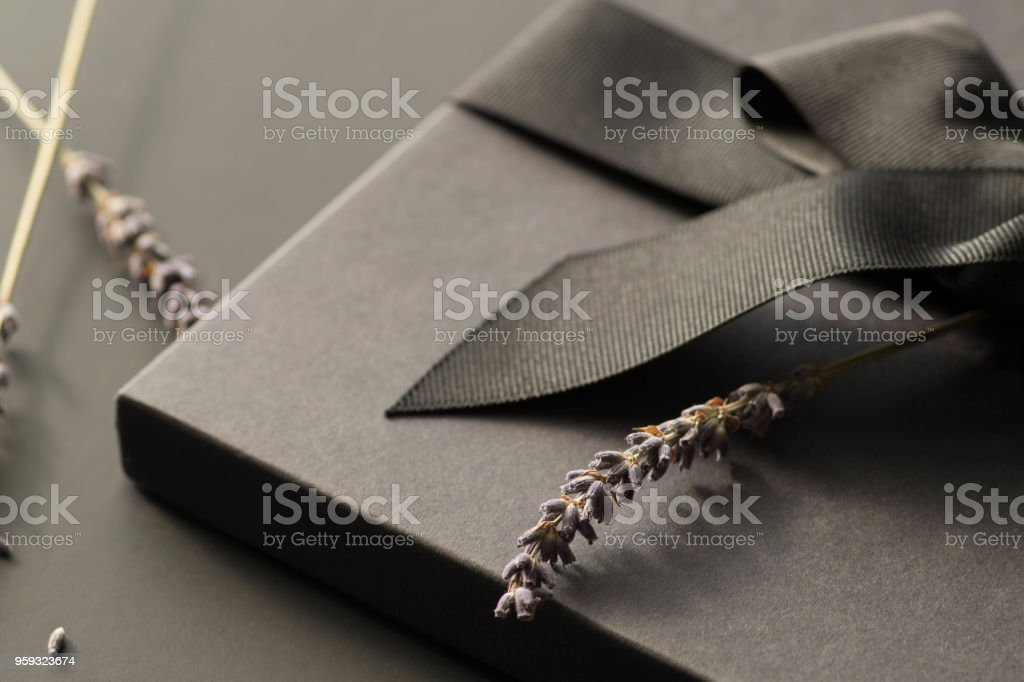 Black gift box on a dark contrasted background, decorated with a textured bow and feathers, creating a romantic atmosphere. Typically used for birthday, anniversary presents, gift cards, post cards. stock photo