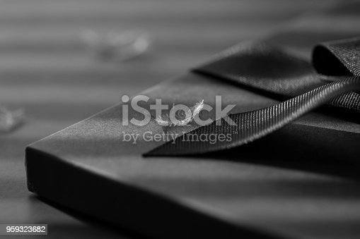 istock Black gift box on a dark contrasted background, decorated with a textured bow and feathers, creating a romantic atmosphere. Typically used for birthday, anniversary presents, gift cards, post cards. 959323682