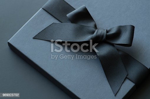 istock Black gift box on a dark contrasted background, decorated with a textured bow and feathers, creating a romantic atmosphere. Typically used for birthday, anniversary presents, gift cards, post cards. 959323702