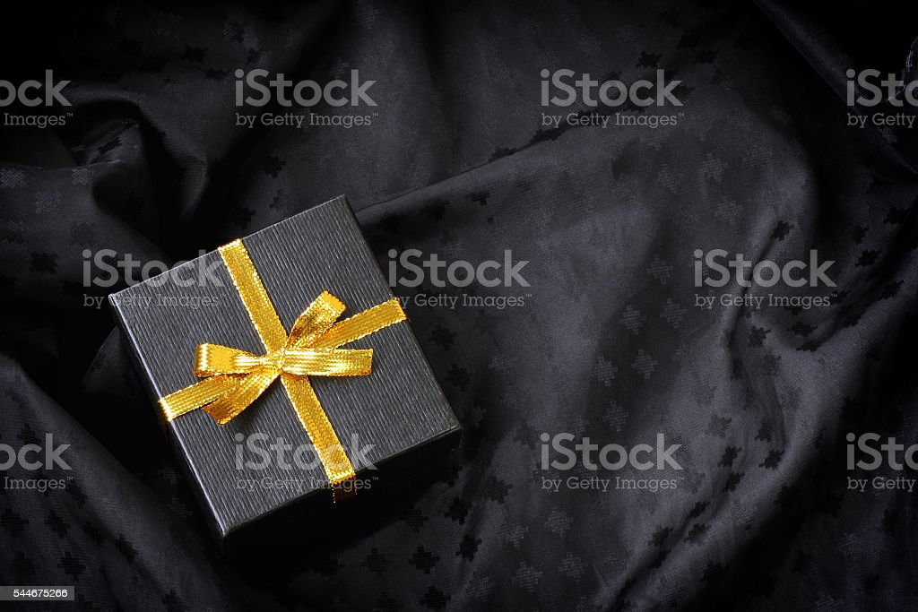 black gift box with golden ribbon bow stock photo