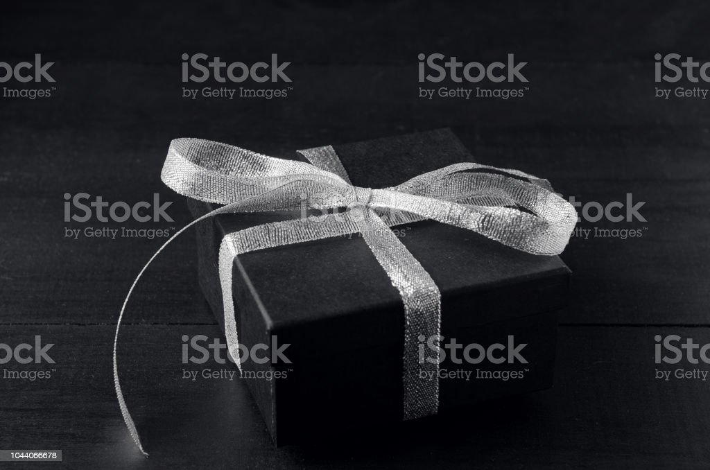 Black gift box with silver ribbon bow on black background.
